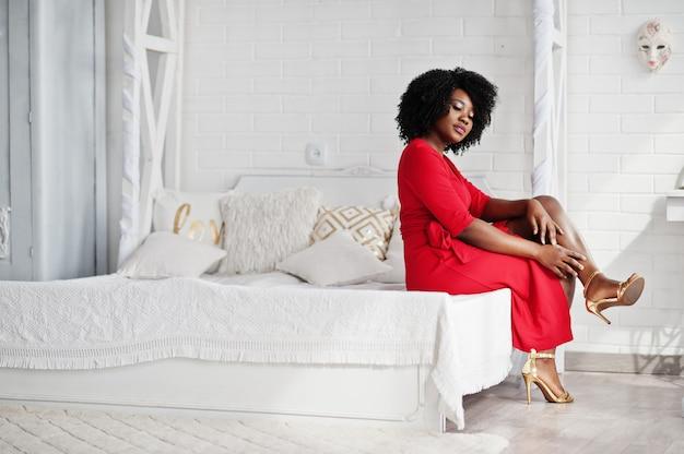 Manier afrikaans amerikaans model in rode schoonheidskleding, de sexy zitting van de vrouwen stellende avondjurk bij bed in witte uitstekende ruimte.