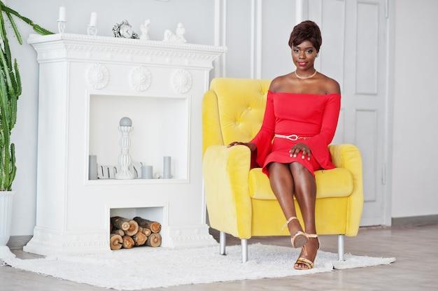 Manier afrikaans amerikaans model in rode schoonheidskleding, de sexy zitting van de vrouwen stellende avondjurk bij gele stoel in witte uitstekende ruimte tegen open haard.