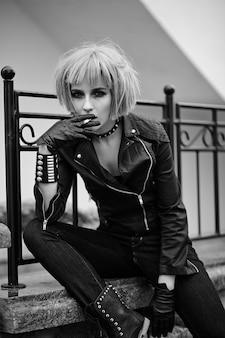Manier blond model in tienerstijl in pruik in openlucht op de straat