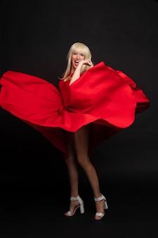 Manier die het vrouwelijke model stellende spelen met golvend rood sexy kledings volledig schot glimlachen