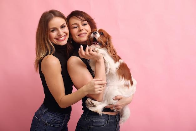 Manier jonge vrouwen die met hond stellen