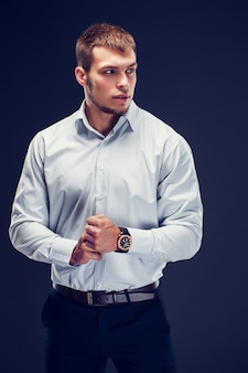 Manier jonge zakenman op donkere achtergrond