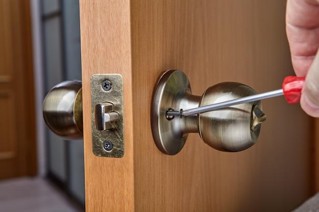 Manier om deurknop te bevestigen met behulp van blootliggende stelschroeven om de handgreep op de draadspil te bevestigen.