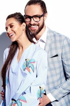 Manierfoto van de knappe elegante man in glazen in kostuum met mooie sexy vrouw in kleurrijke kleding op wit