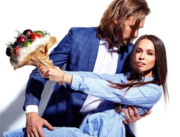 Manierfoto van de knappe elegante man in kostuum met mooie sexy vrouw in kleurrijke kleding op wit