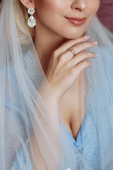Manierfoto van mooie bruid met blond haar in elegante huwelijkskleding in ruimte in de huwelijksochtend
