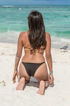Maniermeisje die op het zand knielen die het blauwe overzees op een mooie middag bekijken. vrouw die terug zwempak op haar draagt. terug van aantrekkelijke vrouw kijken naar de zee. zonnehoed met strik op het zand.