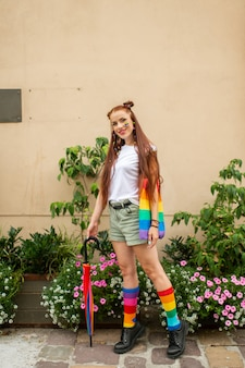 Maniermeisje met lgbt-regenboog het schilderen op haar gezicht die unisex-toebehoren dragen en over muur met bloemen op achtergrond stellen.