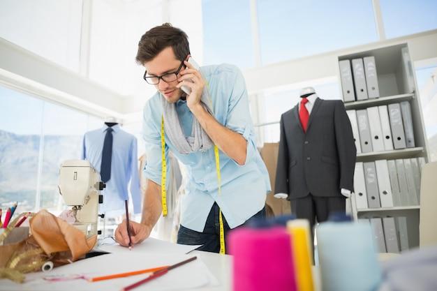 Manierontwerper die aan zijn ontwerpen werkt terwijl op vraag
