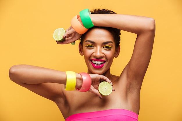 Manierportret van afro amerikaanse vrouw die trendy toebehoren dragen die op camera met twee delen van verse rijpe citroen in handen stellen die, over gele muur worden geïsoleerd