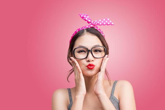 Manierportret van aziatisch meisje met zonnebril die zich op roze bevinden die een kus verzendt.