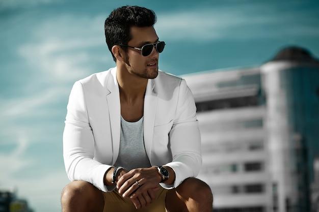 Manierportret van de jonge sexy zakenman knappe modelmens die in toevallig doekkostuum in zonnebril in de straat achter blauwe hemel zitten
