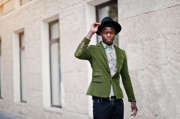 Manierportret van de zwarte afrikaanse amerikaanse mens op groen fluweeljasje en zwarte hoed die op straten van stads achtergrondhuis lopen met vele vensters