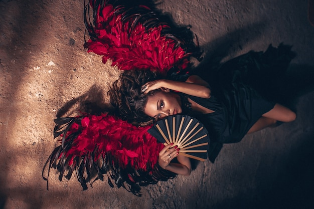 Manierportret van een hartstochtsvrouw die zwarte kleding met rode engelenvleugels dragen en met zwarte ventilator in haar hand. donkere schoonheid mode concept.