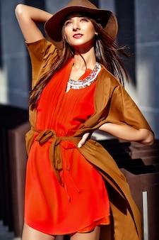 Manierportret van het jonge model van de hippievrouw in de zomer zonnige dag in heldere kleurrijke hipsterkleren in hoed