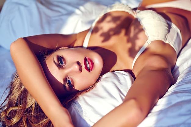 Manierportret van mooi sexy jong volwassen blond vrouwenmodel die witte erotische lingerie dragen die op bed in de ochtendzonsopgang liggen