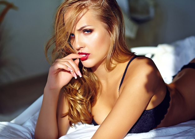 Manierportret van mooi sexy jong volwassen blond vrouwenmodel die zwarte erotische lingerie dragen die op bed bij zonsondergang liggen
