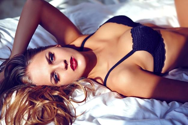 Manierportret van mooie jonge vrouw die zwarte lingerie op wit bed dragen