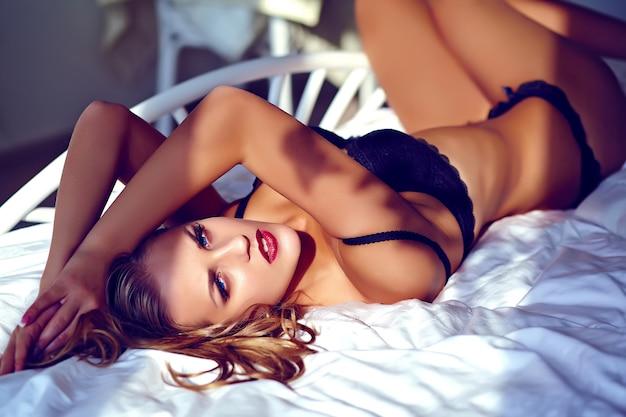 Manierportret van mooie sexy jonge vrouw die zwarte lingerie op bed dragen