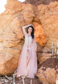 Manierportret van sexy donkerbruine vrouw in de kleding van het boudoirkant met juwelen. de ochtend van de bruid. fine art bruiloft. mooie dame met lang krullend haar van het huwelijkskapsel en bruids make-up.