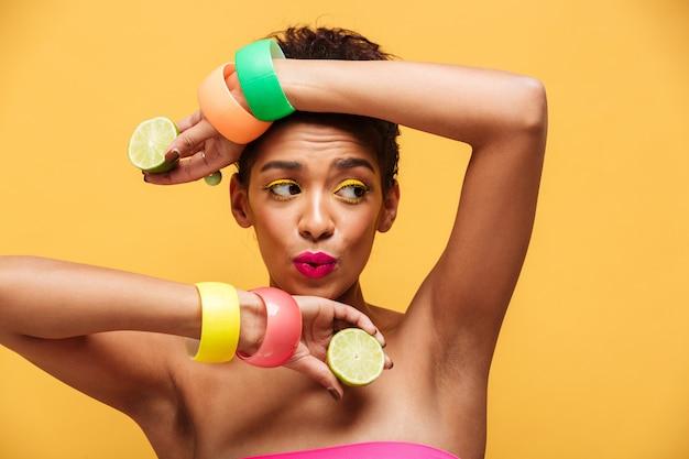Manierportret van speelse mulatvrouw die trendy toebehoren dragen die op camera met twee delen van verse rijpe die citroen stellen, over gele muur wordt geïsoleerd