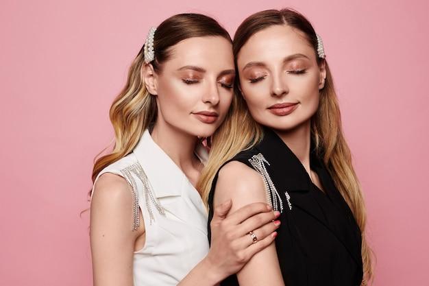 Manierportret van twee mooie jonge tweelingen modelmeisjes met trendy make-up die bij roze achtergrond wordt geïsoleerd. schoonheidsportret van tweelingvrouwen met modieuze accessoires, perfecte make-up en een gladde huid