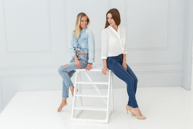 Manierportret van vrouwen in jeans in lichte studio