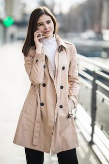 Maniervrouw die en op de mobiele telefoon in een stadsstraat lopen spreken