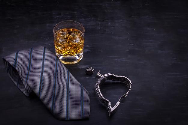 Mannelijk concept voor vaderdag. bind, horloges, manchetknopen en een glas whisky met ijs