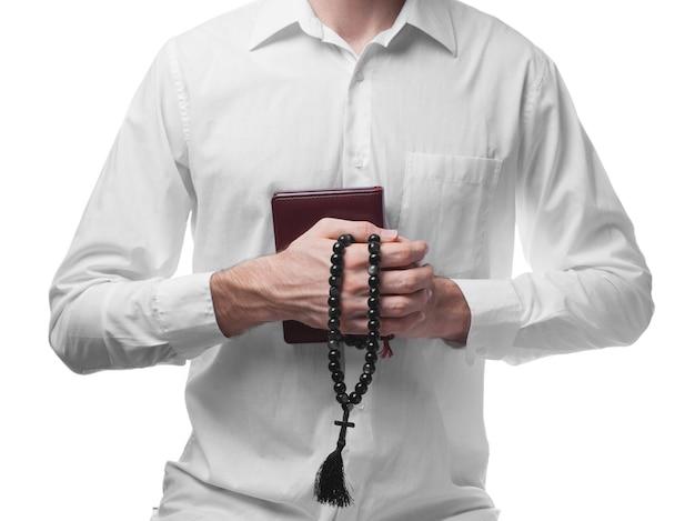 Mannelijk gebed in wit overhemd met geïsoleerde bijbel en parels