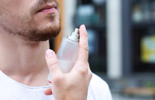 Mannelijk geurconcept. knappe man beveelt aangenaam aroma aan voor mannen