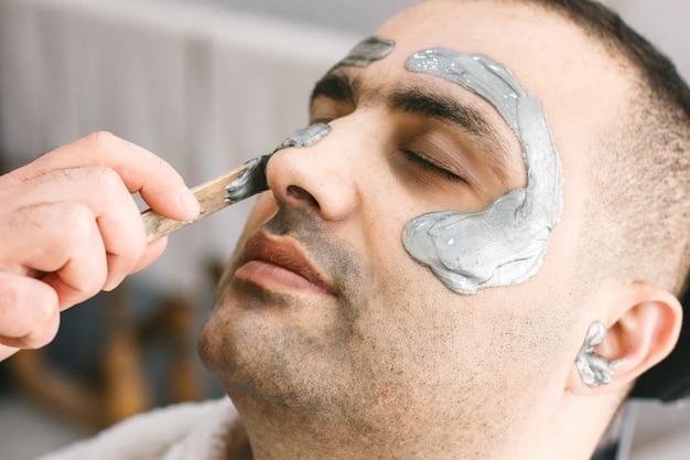 Mannelijk gezicht waxen. kapper verwijdert haar door zich uit het gezicht van de turkse man te trekken.