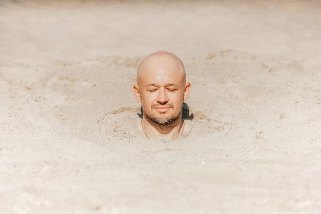 Mannelijk kaal hoofd boven zand. man levend begraven in de woestijn. close-upportret die van grappige kerel zonnebaden met lichaam nemen onder zand.