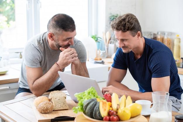 Mannelijk kaukasisch vrolijk paar die gelukkige ontbijtbespreking hebben