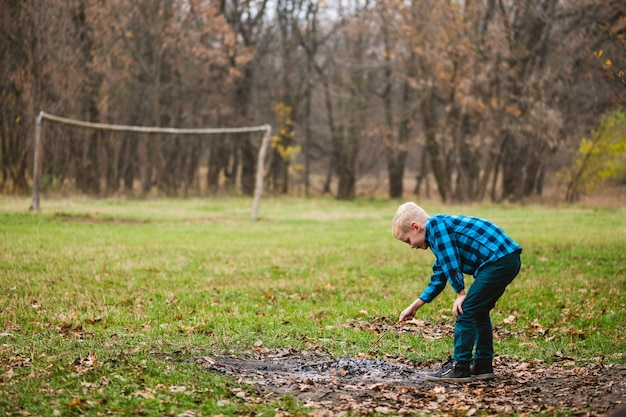 Mannelijk kind tijdens wandeling in herfstbos spelen met houten takje en vuuras in droge gevallen bladeren, nieuwsgierig actief jeugdconcept