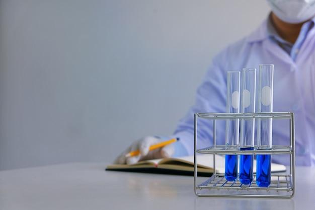 Mannelijk medisch of wetenschappelijk laboratorium onderzoeker voert tests uit met blauwe vloeistof in laboratorium. laboratorium apparatuur en wetenschappelijke experimenten concept.