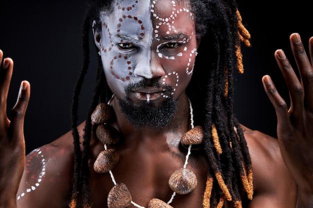 Mannelijk model doet ritueel geïsoleerd over zwarte muur