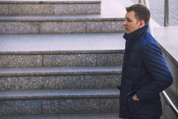 Mannelijk model in trendy, moderne warme jeugdjas in het stadslandschap op het oppervlak van trappen