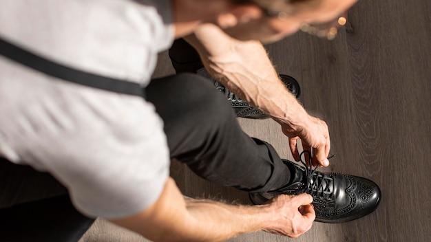 Mannelijk model met krullend haar bindt zijn schoenveters