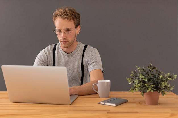 Mannelijk model met krullend haar dat aan zijn laptop werkt