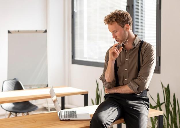 Mannelijk model met krullend haar dat zijn laptop bekijkt