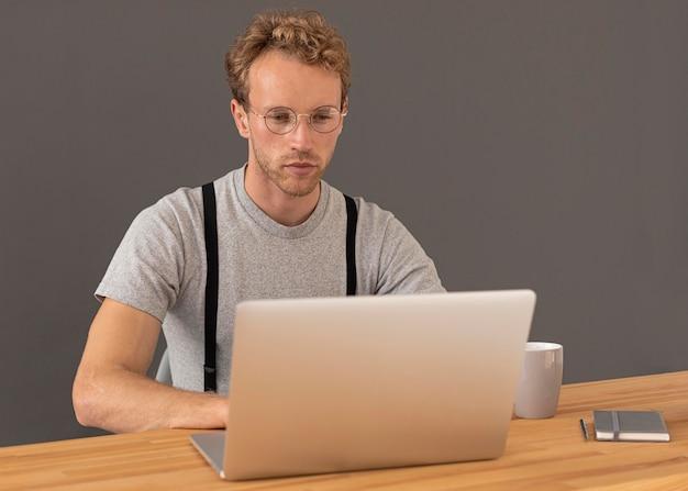 Mannelijk model met krullend haar met behulp van zijn laptop