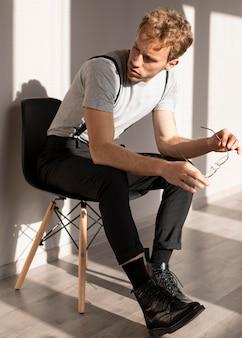 Mannelijk model met krullend haar, zittend op een stoel en wegkijken