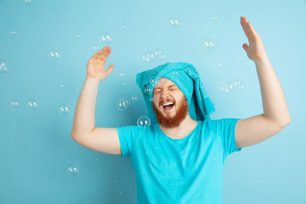 Mannelijk model met natuurlijk rood haar dansen in bubbels, ziet er gek gelukkig uit