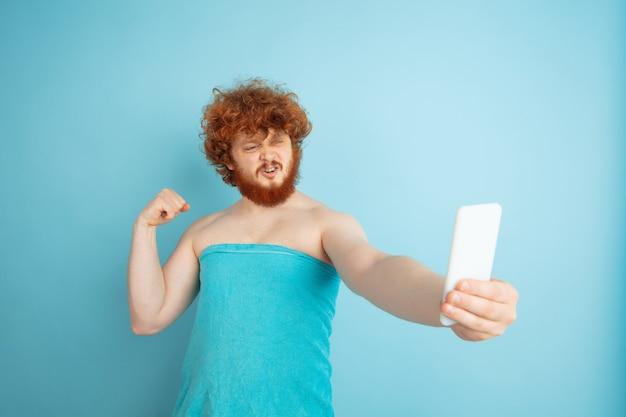 Mannelijk model met natuurlijk rood haar dat selfie in handdoek neemt