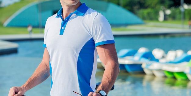 Mannelijk model promotie watersportoutfits naast een zwembad.