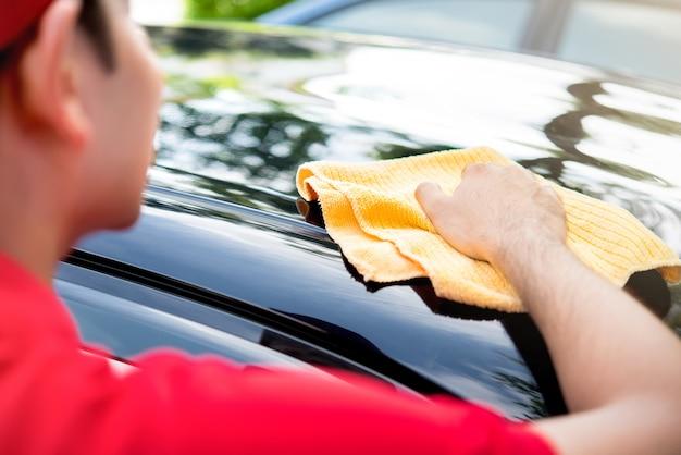 Mannelijk personeel in rood eenvormig schoonmakend autodak met microfiberdoek