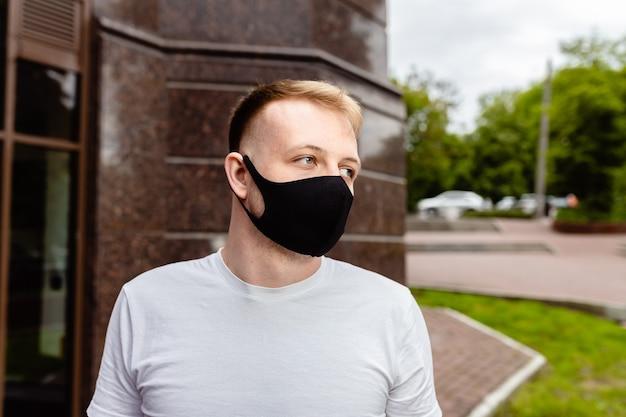 Mannelijk portret. een man met een zwart masker. quarantaine in de stad.