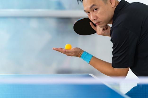 Mannelijk speelpingpong met racket en bal in een sporthal