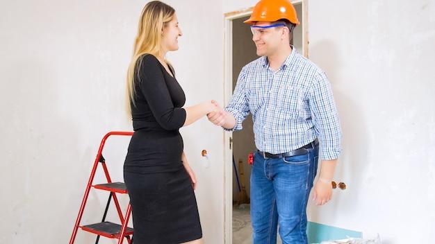 Mannelijke aannemer die handen schudt met jonge zakenvrouw in huis in aanbouw.